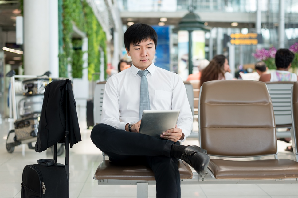 Asian businessman using digital tablet while waiting in lounge at airport.Business travel concept.; Shutterstock ID 475645810; Departmental Cost Code : 162800; Project Code: GMKT_SUP_4.9.1E; PO Number: GBLMKT/2015-082